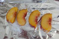 Pfirsichscheiben auf einer feuerfesten Unterlagen verteilen und mit Zucker bestreuen.