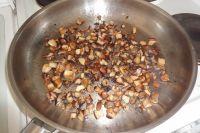 Die Pilze verlieren durch das Schmoren viel Wasser und schrumpfen gut auf die Hälfte zusammen. Die Pilze nun zusätzlich mit etwas Pfeffer und Chilipulver würzen.