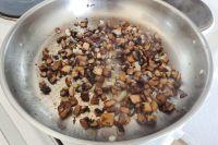 Sobald die Pilze schön braun sind, gehackte Zwiebeln hinzugeben. Solange weiter schmoren, bis die Zwiebeln glasig sind.